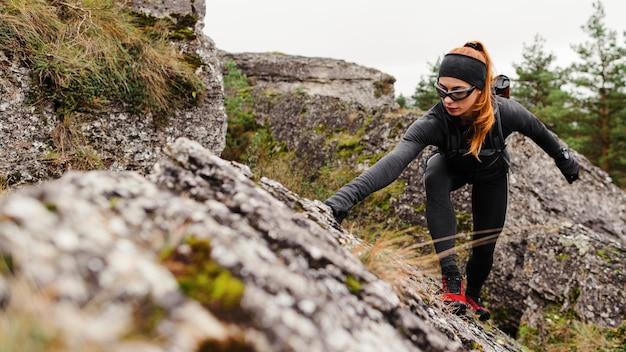 Женский спортивный бегун, лазание по камням, вид спереди