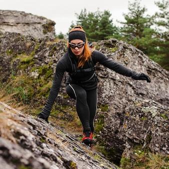Женский спортивный бегун, лазание по камням, длинный выстрел
