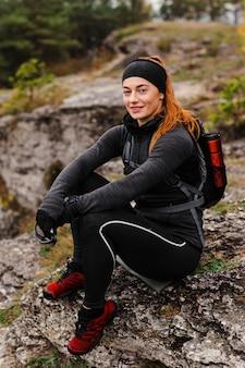 岩の上に座っている女性のスポーティなジョガー