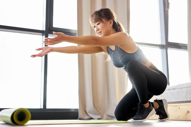 女性はヨガマットを広げ、自宅でエクササイズをします。昼間にスポーツに従事するスポーツウェアの女性。 aportと健康的なライフスタイルのコンセプト
