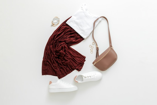 Female spring look summer outfit burgundy skirt white shoes sneakers white basic tshirt waist bag. folded fly clothes for women fashion urban basic outfit with accessories. top view.