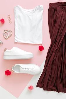 女性の春のルック夏の服のスカートの靴スニーカーの基本的なtシャツバッグ。ピンクの背景に化粧品を構成するアクセサリーの花と女性のファッション都市の基本的な衣装のための折り畳まれた服。上面図。