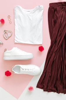 Female spring look summer outfit skirt shoes sneakers basic tshirt bag. folded clothes for women fashion urban basic outfit with accessories flowers make up cosmetics on pink background. top view.