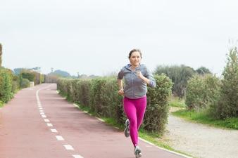 Женский спринтер быстро бегает по дорожке стадиона
