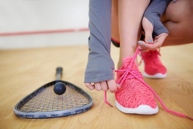 Женский игрок в сквош, связывающий спортивную обувь