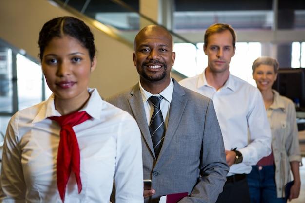 空港ターミナルに立っている女性スタッフと乗客