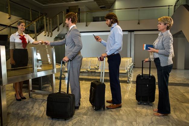 Personale femminile che controlla la carta d'imbarco dei passeggeri al banco di registrazione