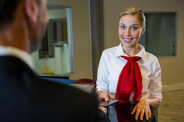 ビジネスマンに搭乗券を与える女性スタッフ