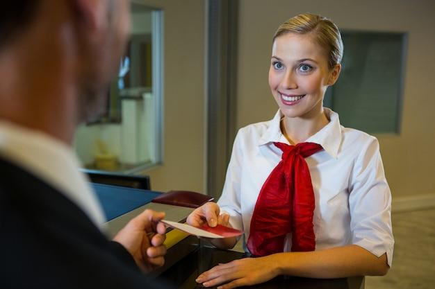 Женский персонал, дающий бизнесмену посадочный талон