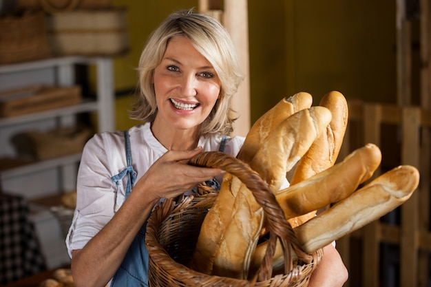 Female staff holding basket of baguettes in bakery section