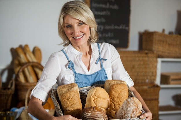 Female staff holding basket of bread in bakery section