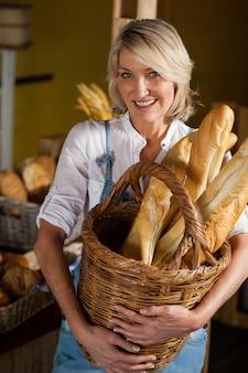Женский персонал держит корзину багетов в пекарне