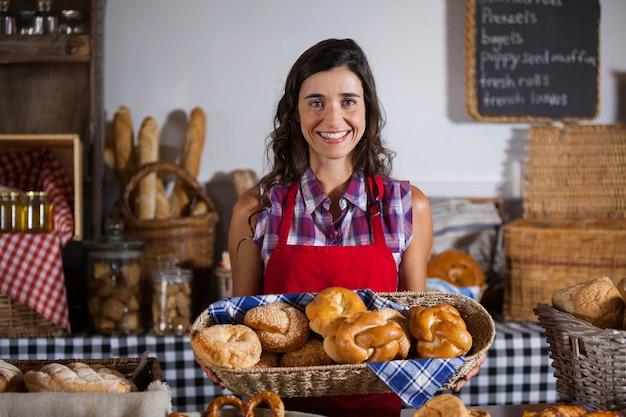 Женский персонал держит корзину сладких продуктов в пекарне