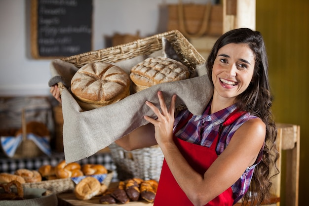 Female staff holding basket of sweet foods in bakery section