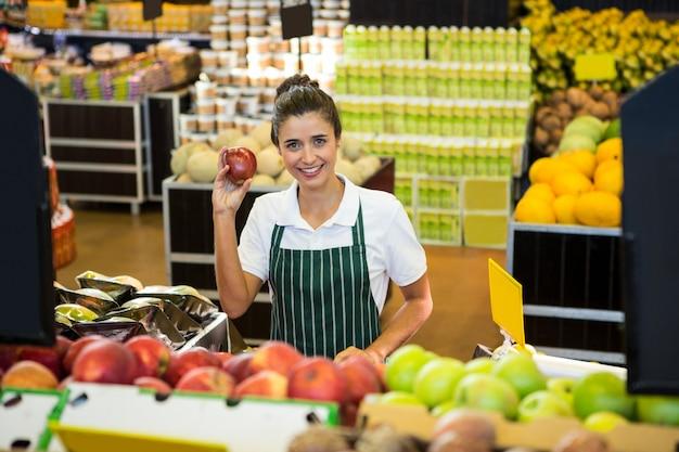スーパーのオーガニックセクションで果物を保持している女性スタッフ