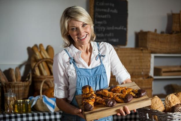 Женский персонал держит сладкие блюда в пекарне