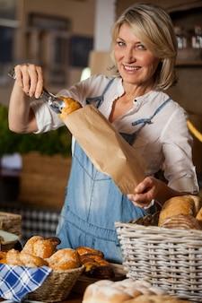 Женский персонал, упаковывающий сладкую еду в бумажный пакет