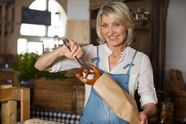Female staff packing sweet food in paper bag
