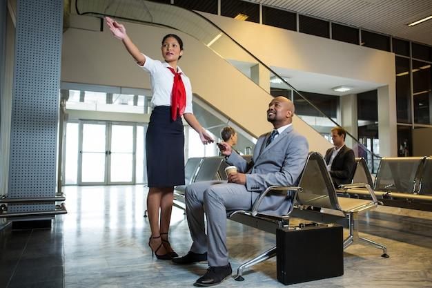 Женский персонал показывает направления к бизнесмену