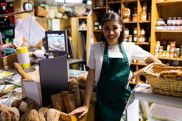 Женский персонал стоит у прилавка с хлебом
