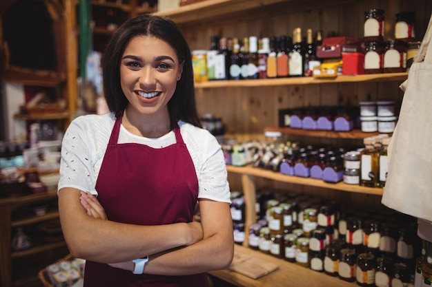 Женский персонал, стоя со скрещенными руками в супермаркете