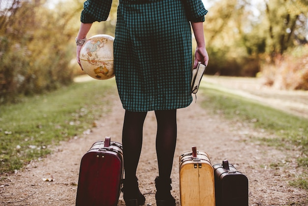 Female standing on an empty road  near her old suitcase while holding the bible and a desk globe