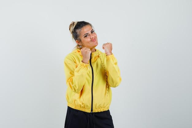 Donna in piedi nella posa di lotta in tuta sportiva e guardando fiducioso, vista frontale.