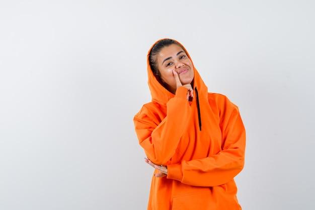 オレンジ色のパーカーでポーズを考えて立っていると陽気に見える女性