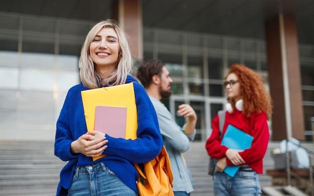入学キャンペーン中に大学の外に立っている女性