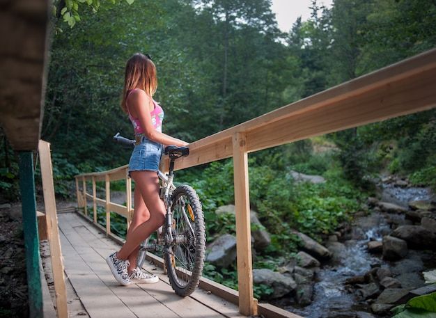 Female standing with bicycle on wooden bridge over mountain river