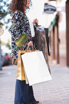 Female standing with shopping bags on street