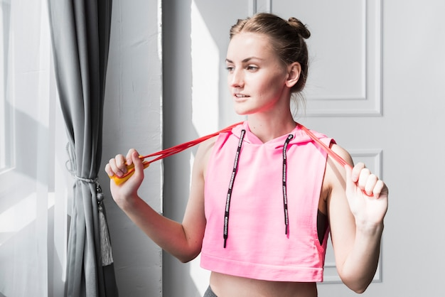 Female standing with skipping rope in hands