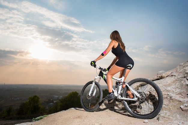 Female starting to ride on bicycle on the mountain hill