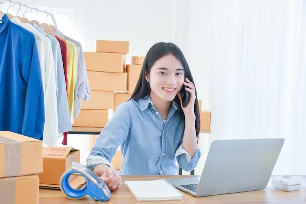 Владелец малого бизнеса женского запуска, работающий с портативным компьютером в офисе