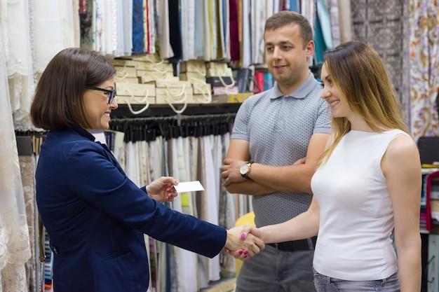 여성 상점 주인이 젊은 부부에게 명함을 제공합니다.