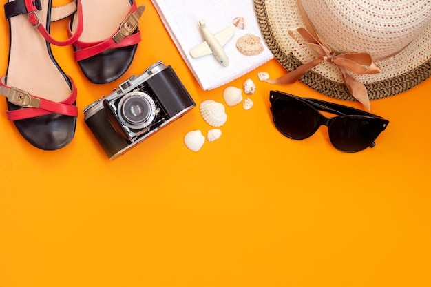 Female straw hat black sunglasses old vintage retro camera sandals towel toy plane and seashells isolated on a bright color orange wall