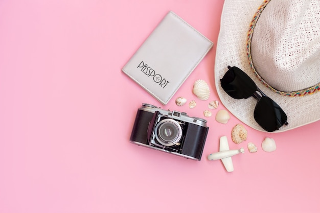 Female straw white hat passport black sunglasses old vintage retro camera toy mini plane and seashells isolated on a light color pink wall