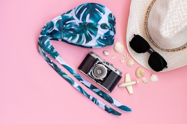 Female straw white hat swimsuit with palm leavesblack sunglasses old vintage retro camera toy plane and seashells isolated on a light color pink wall
