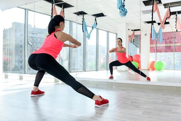 Женское тело растяжения в тренажерном зале. концепция здорового образа жизни. спорт для всех