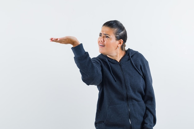 Female stretching hand in questioning manner in hoodie and looking angry. front view.