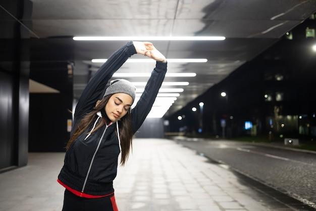 Женщина протягивает обе руки перед тренировкой на открытом воздухе