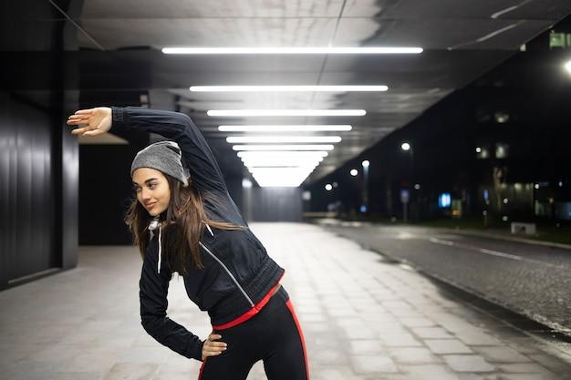 Женщина растягивает левый бок перед ночной пробежкой по городу
