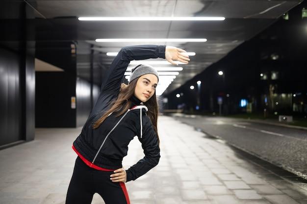 Женщина растягивает правый бок перед тренировкой в городе