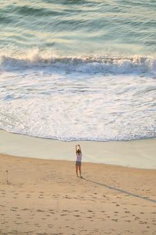 朝の陽光、コパカバーナビーチ、ブラジルの砂浜でストレッチ女性