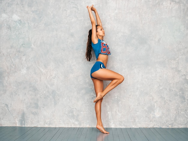 Female stretching out before training near gray wall in studio