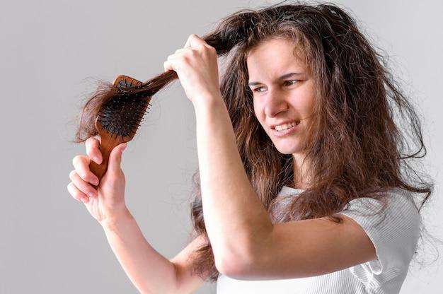 Donna che lotta per spazzolare i capelli