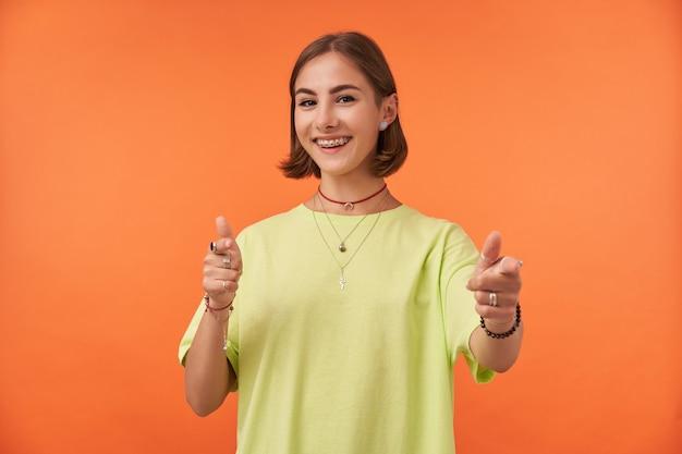 여성 학생, 짧은 갈색 머리 웃 고 오렌지 벽 위에 가리키는 매력적인 젊은 아가씨. 맞아요. 녹색 티셔츠, 치아 교정기 및 팔찌 착용