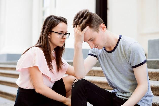 Студентка успокаивает своего друга мужского пола. подросток расстроен, сидит на лестнице, его друг пытается его успокоить