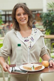 Женщина-студент с подносом для еды в столовой