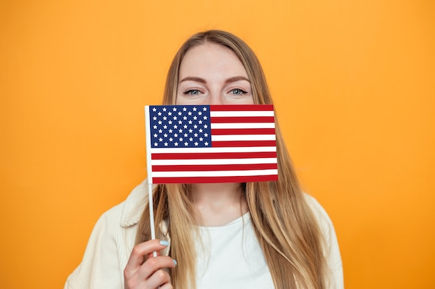 Female student covering her face with a small american flag